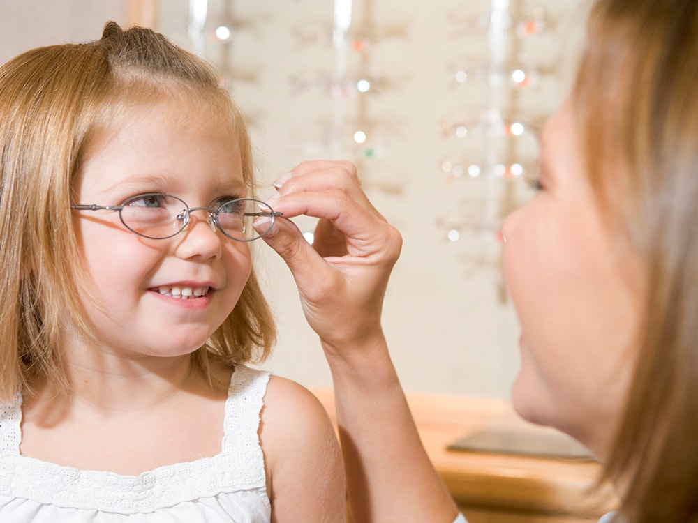 Woman putting glasses on a young girl at the eye doctor.
