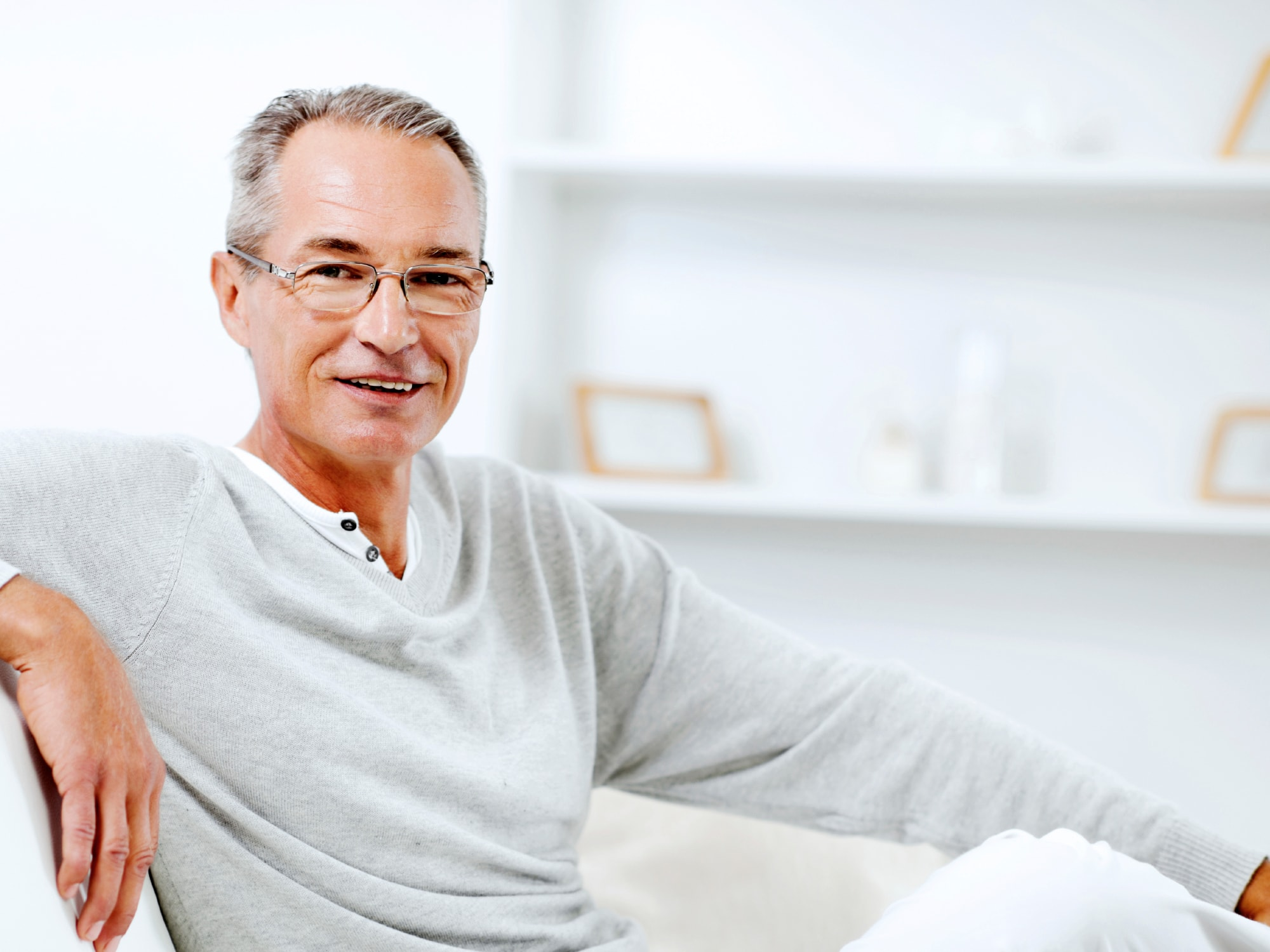 Mature man using sitting on the sofa at home and looking at the camera.